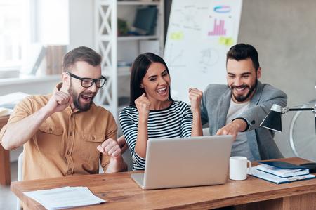 Succes vieren. Drie gelukkige bedrijfsmensen in slimme vrijetijdskleding die laptop en het gesturing bekijken Stockfoto