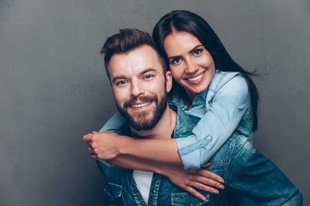 beautiful sex: Happy to be together. Handsome young man piggybacking beautiful woman and smiling while standing against grey background