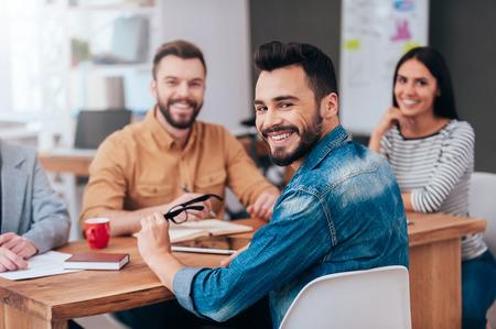 jornada de trabajo: Disfrutar de buena días de trabajo juntos. Grupo de hombres de negocios confidentes en ropa de sport elegante que se sienta en la mesa y sonriendo