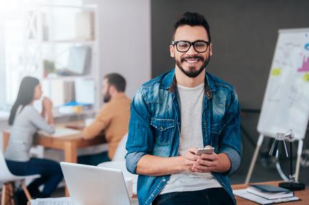 Voller neuer großartige Ideen. Überzeugter junger Mann Smartphone halten und in die Kamera mit Lächeln, während seine Kollegen im Hintergrund arbeiten Lizenzfreie Bilder