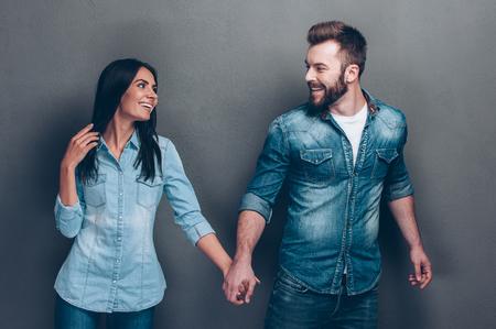 sexo pareja joven: ¡Sígueme! Tiro del estudio de la hermosa joven pareja en jeans caminar juntos y de la mano Foto de archivo