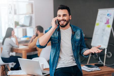 Partage de bonnes nouvelles. Confiant jeune homme souriant parler au téléphone mobile et gestes pendant que ses collègues travaillant dans le fond Banque d'images - 48960237