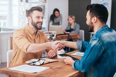 confianza: ¡Bien hecho! Dos jóvenes confía en estrechar la mano y sonriendo mientras está sentado en el escritorio en la oficina con dos personas trabajando en segundo plano Foto de archivo