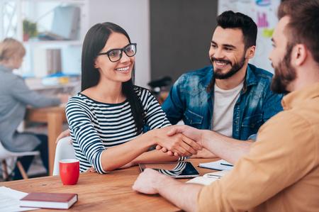 Bem-vindo a bordo! Confiante jovem mulher e um homem apertando as mãos e sorrindo enquanto está sentado na mesa no escritório