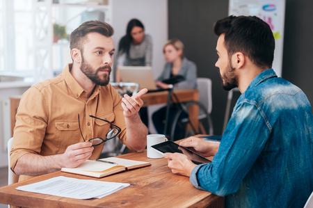 一緒に解決策を見つけます。自信を持って 2 つの若い男性話と背景で働く 2 人の同僚とオフィスで机に座っている間は身振りで示す