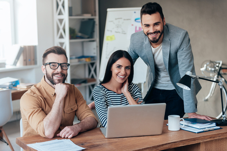 Successful team. Three confident business people in smart casual wear looking at camera and smiling while sitting at the desk in office Stock Photo