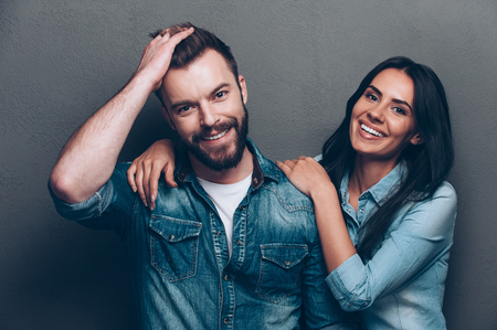We are better when we together. Studio shot of beautiful young couple in jeans wear standing close to each other and looking at camera with smile