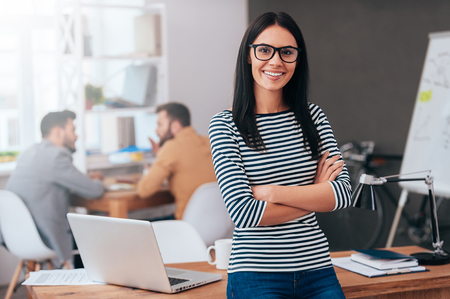 smiling man: Confident and successful leader. Confident young woman keeping arms crossed and looking at camera with smile while her colleagues working in the background Stock Photo