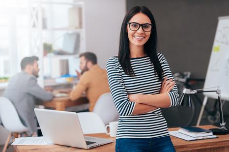 Selbstbewusste und erfolgreiche Marktführer. Überzeugte junge Frau, die Arme gekreuzt und Blick auf Kamera mit Lächeln, während ihre Kollegen in den Hintergrund arbeiten