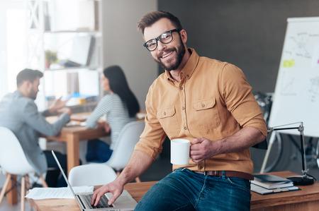 Confiant professionnel de l'informatique. Confiant jeune homme travaillant sur ordinateur portable et souriant tandis que ses collègues de parler dans le fond Banque d'images - 48962801