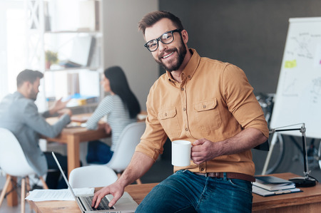 Confident IT professional. Confident young man working on laptop and smiling while his colleagues talking in the background Stock Photo