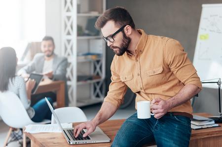 confianza: Profesional de TI en el trabajo. Hombre joven confidente que trabaja en la computadora portátil mientras que sus colegas hablando en el fondo