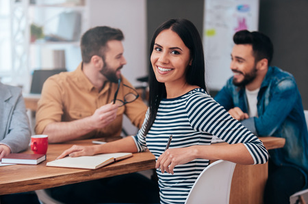 Enjoying work in team. Group of business people in smart casual wear discussing something while one woman looking over shoulder and smiling Archivio Fotografico