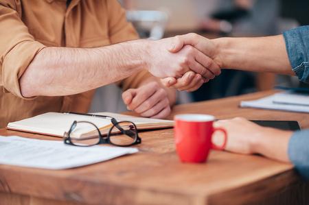 Dichtung einen Deal. Close-up von zwei Männern, die Hände schütteln, während auf dem hölzernen Schreibtisch sitzen