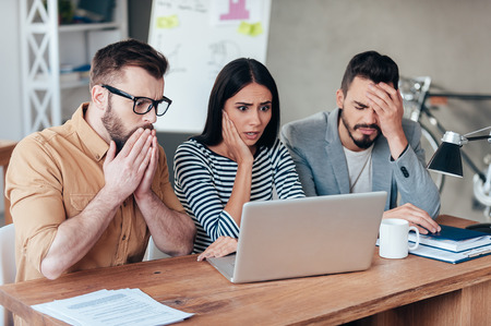 beard woman: Oh no! Three frustrated young business people in smart casual wear looking at the laptop and expressing negativity Stock Photo
