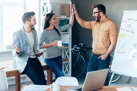 축하: 성공을 축하합니다. 행복 한 젊은 남자가 사무실에서 화이트 보드 근처에 서와 그의 동료들에게 하이 파이브를주는
