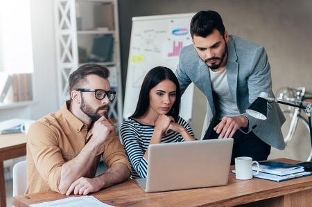 Eles precisam de uma consultoria especializada. Grupo de empresários confiantes em desgaste smart casual olhar para o portátil junto