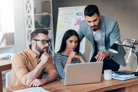 Ils ont besoin d'un avis d'expert. Un groupe de gens d'affaires confiants de mode casual smart regardant l'ordinateur portable ensemble