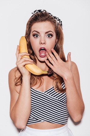 Fruity gossips.  Beautiful young woman holding banana like a phone and covering her mouth with hand while standing against white background