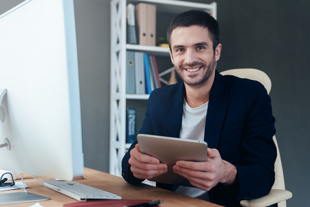 only man: Technologies making life easier. Confident young man holding digital tablet and smiling while sitting at his working place in office