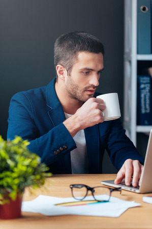 no time: No time for break. Handsome young man in smart casual wear working on laptop and holding coffee cup while sitting at his working place in office