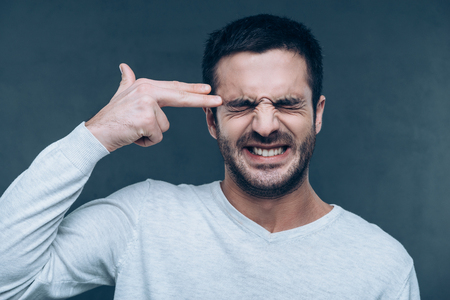 Bang! Frustrated young man gesturing finger gun near head and keeping eyes closed while standing against grey background