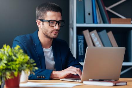 Geschäftsmann bei der Arbeit. Konzentrierte junge Mann arbeitet am Laptop, während an seinem Arbeitsplatz im Büro sitzen