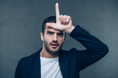 l hand: Looser. Portrait of beautiful young man gesturing L sign while standing against grey background