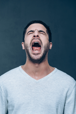 of the mouth: Man shouting. Furious young man keeping eyes closed and mouth open while standing against grey background