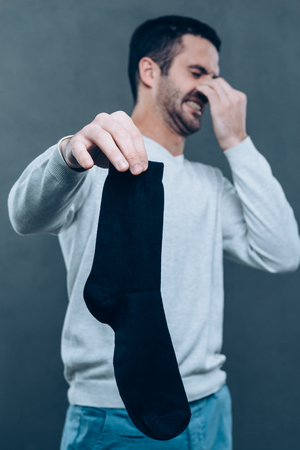 expressing negativity: Awful smell! Frustrated young man expressing negativity and covering nose with fingers while holding black sock and standing against grey background