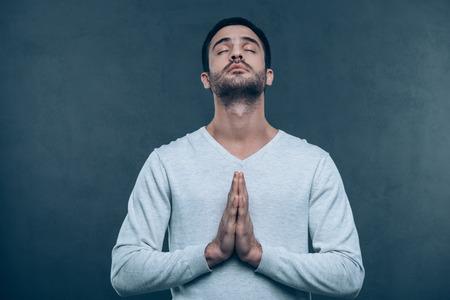 clasped: Man praying. Studio shot of handsome young man praying while holding hands clasped and keeping eyes closed