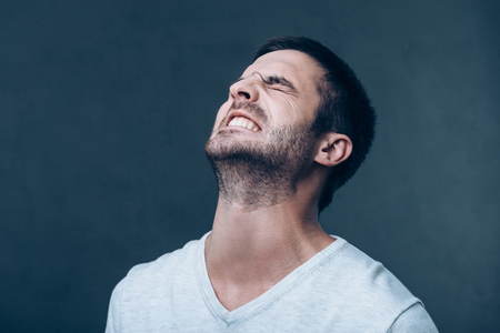 expressing negativity: Oh no! Frustrated young man keeping eyes closed and expressing negativity while standing against grey background Stock Photo