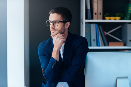 solutions: Thinking about solution. Confident young man in smart casual wear holding hand on chin and looking at camera while leaning at computer monitor in office