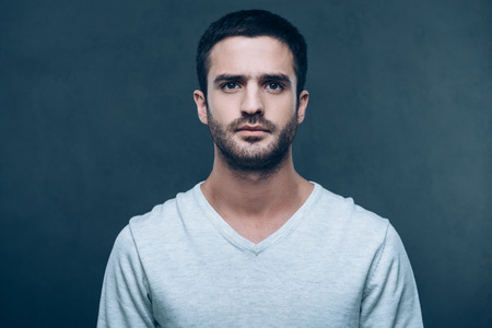 masculinity: Portrait of masculinity. Handsome young man looking at camera while standing against grey background