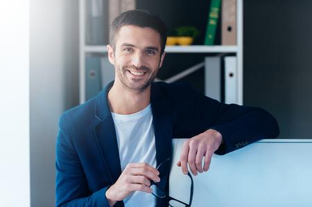 especialista em TI confiante. Homem novo confiável transportando óculos e sorrindo enquanto se inclina para o monitor do computador no escritório