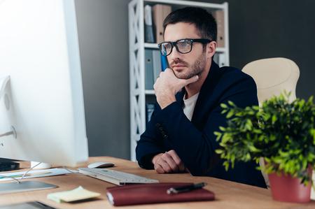 hombre pensando: Pensando en solución. Joven reflexivo en casual elegante mano que sujeta el desgaste en la barbilla y mirando la pantalla del ordenador mientras está sentado en su lugar de trabajo en la oficina