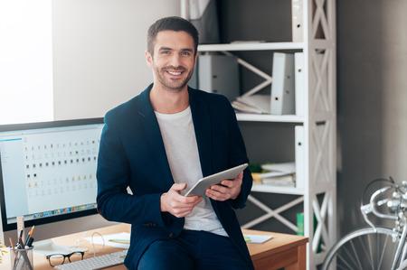 Vertrouwen business expert. Zekere jonge mens die digitale tablet en lachend terwijl leunend op het dek in het kantoor