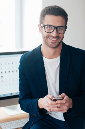 successful man: Smart and confident. Confident young man holding smart phone and smiling while leaning at the office desk