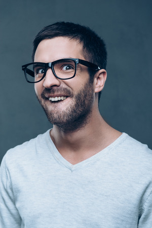 making a face: Like a nerd. Young nerd man in eyeglasses making a face while standing against grey background Stock Photo