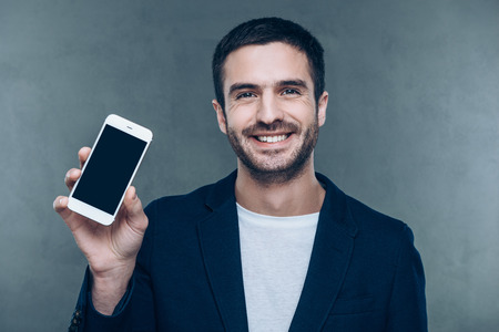 showing: Look at my new smart phone! Cheerful young man holding mobile phone and smiling while standing against grey background