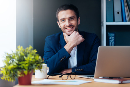 Confident and inspired. Confident young man holding hand on chin and smiling while sitting at his working place in office