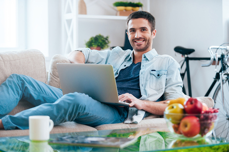 Carefree time at home. Handsome young man working on laptop and smiling while lying on the couch at home Banco de Imagens