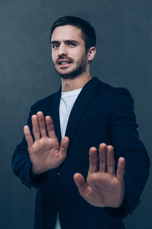 no way: No way! Frustrated young man looking at camera and gesturing while standing against grey background Stock Photo