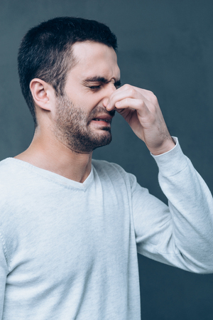 expressing negativity: Awful smell! Frustrated young man expressing negativity and covering nose with fingers while standing against grey background Stock Photo