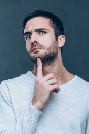 no way: No way! Frustrated young man touching his chin with finger and looking at camera while standing against grey background Stock Photo