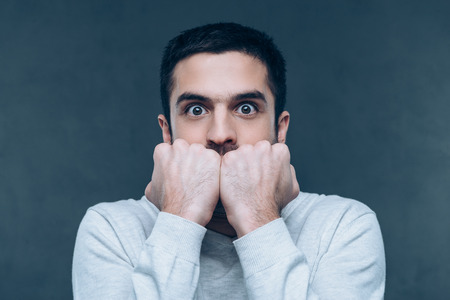 grey nails: Feeling shocked. Terrified young man looking at camera and biting nails while standing against grey background Stock Photo