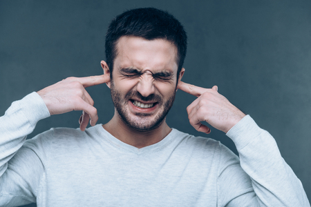Too loud sound! Frustrated young man expressing negativity while covering ears with hands and standing against grey background