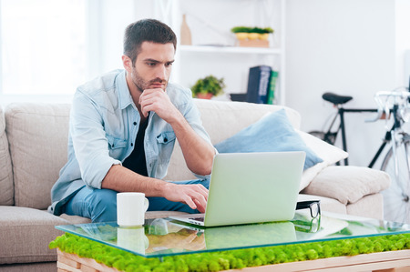 surfing the net: Surfing net at home. Handsome young man working on laptop while sitting on the couch at home