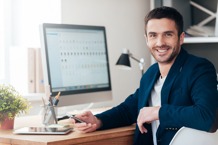 only man: Confident and successful. Confident young man holding smart phone and smiling while sitting at his working place in office