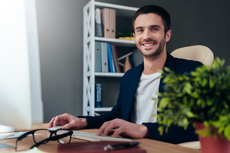 man only: Enjoying good working day. Confident young man working on computer and smiling while sitting at his working place in office Stock Photo